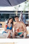 fröhliches junges Paar sitzt mit Gläsern Erfrischungsgetränk auf einem Liegestuhl und blickt in die Kamera