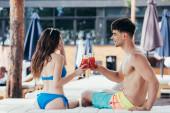 glückliches junges Paar klimpert im Liegestuhl mit einem Glas Erfrischungsgetränk