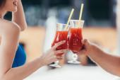 abgeschnittene Ansicht einer lächelnden jungen Frau, die mit ihrem Freund Gläser mit Erfrischungsgetränken klappert