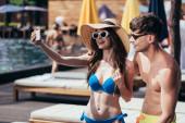 vidám fiatal nő napszemüveg és Szalmakalapot vesz selfie a jóképű barátja