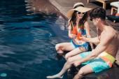 Veselý mladý pár cinkuje sklenicemi s osvěžující sklenicí nápojů při sezení na poolové straně