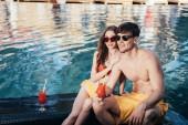 glückliches junges Paar schaut weg, während es am Pool mit einem Glas Erfrischungsgetränk sitzt