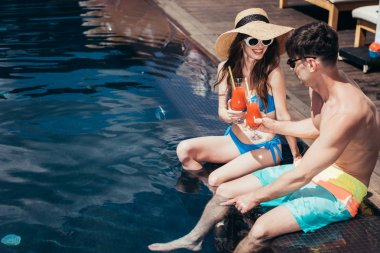 cheerful young couple clinking glasses with refreshing drink while sitting on poolside