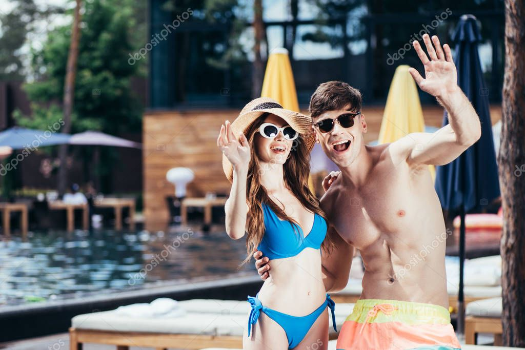 Cheerful young couple in sunglasses waving hands and looking at camera