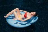 szép fiatal nő a fürdőruhában napozás az úszó gyűrű a medencében