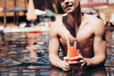 cropped view of handsome young man relaxing on poolside with glass of refreshing drink