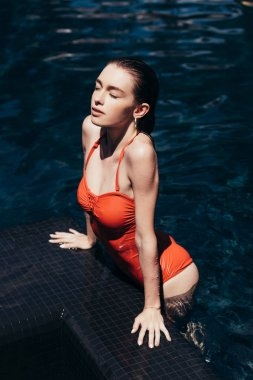 beautiful young woman sunbathing on poolside with closed eyes