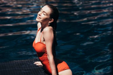 happy beautiful woman in swimsuit relaxing on poolside with closed eyes