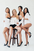 full length view of four smiling sexy multiethnic women wearing heels near wooden chair on grey