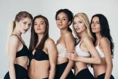 Pět sexy multietnických mladých žen ve spodním prádle objímající izolované na šedé