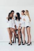 pohled na sexy multietnické feministy na podpatcích a bílých kočkách s úsměvem na šedé