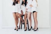 oříznutý pohled na pět sexy dívek v patách na šedé