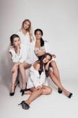 čtyři sexy multietnická feministka s podpatky a bílými košile na šedé