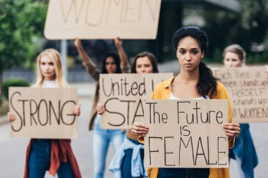 serious african american feminist holding placard with inscription the future is female near women on street