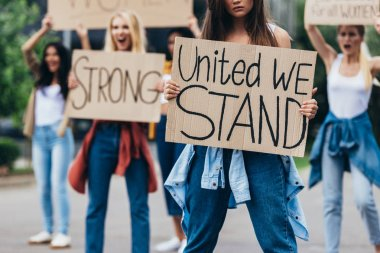 cropped view of girl holding placard with inscription united we stand near feminists on street