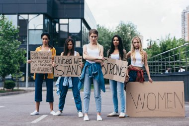full length view of multiethnic feminists holding placards with slogans on street