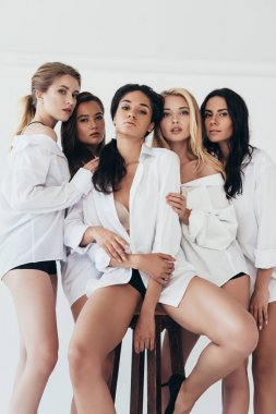 Five sexy multiethnic girls in white shirts looking at camera on grey stock vector