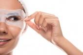 Fotografie Teilansicht der nackten jungen Frau in kosmetischem Haarband mit Gesichtsmaske lächelnd isoliert auf weiß