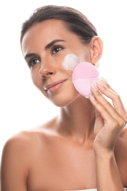 Nude young woman with cream on face using facial cleansing brush isolated on white stock vector