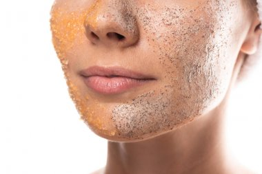 cropped view of young woman with scrub on face isolated on white