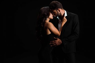 attractive girl touching suit of passionate bearded man isolated on black