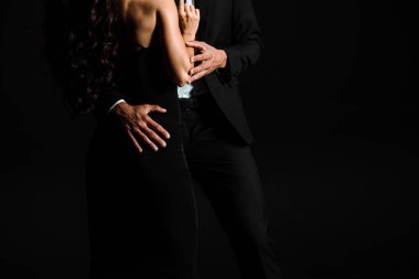 cropped view of man in formal wear hugging and touching young woman in dress isolated on black
