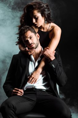 passionate girl standing and hugging handsome bearded man on black with smoke