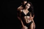 muž objímat sexy ženskou v krajním prádle izolovaně na černém