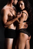 young woman in lace lingerie hugging sexy shirtless man isolated on black