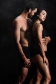 nečistý muž, který objímá mladou sexy ženu stojící na černém s kouřem