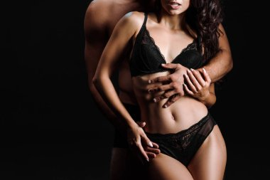 cropped view of shirtless man hugging sexy girl in underwear isolated on black
