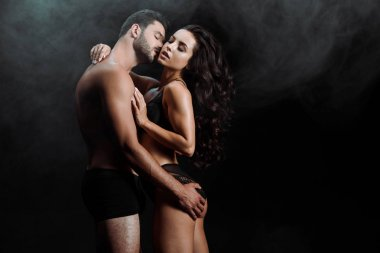 handsome man kissing and touching buttocks of woman on black with smoke