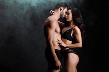 young woman hugging handsome and shirtless man on black with smoke
