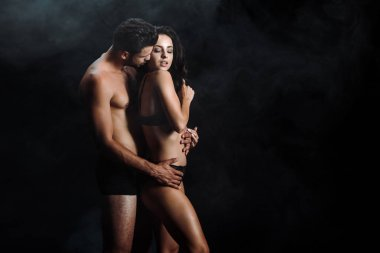 shirtless man kissing sexy young woman standing on black with smoke
