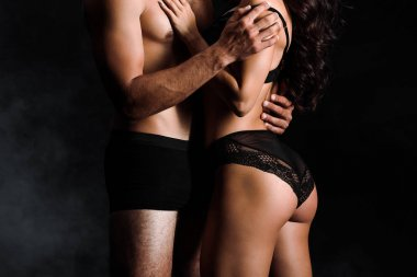 cropped view of shirtless man touching sexy woman in lace underwear on black with smoke