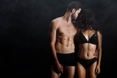 handsome and shirtless man hugging happy girl in lingerie on black with smoke