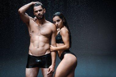 Wet girl in underwear standing near shirtless man under raindrops on black stock vector