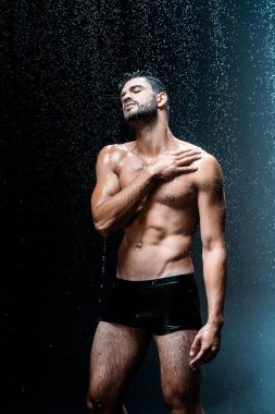shirtless and wet man standing under raindrops on black