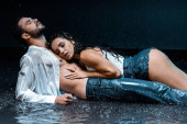 Photo sexy and wet woman lying with handsome boyfriend under raindrops on black