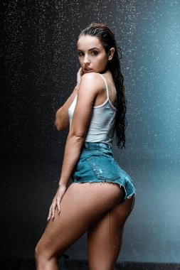 sexy woman standing and looking at camera under raindrops on black ac