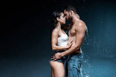 sexy shirtless man hugging attractive woman near splash of water on black
