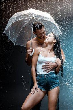 happy bearded man hugging cheerful girlfriend and holding umbrella on black