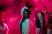 girl dancing in nightclub during rave with pink smoke
