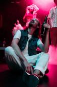 Fényképek boldog ember a napszemüveg, üveg alkohol alatt rave a nightclub