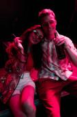 šťastný muž s pivem u dívky s cigaretou v nočním klubu během rave