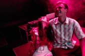 man and young woman laughing during rave party in nightclub