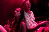 uomo e giovane donna seduta insieme durante la festa rave in discoteca