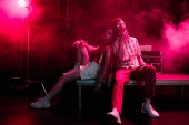 man and young woman sitting together during rave party in nightclub with pink smoke