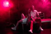 férfi és fiatal nő ül együtt a rave Party-ben a nightclubban rózsaszín füst