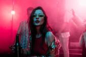 Fényképek gyönyörű lány gazdaság sört nightclub és tánc alatt rave